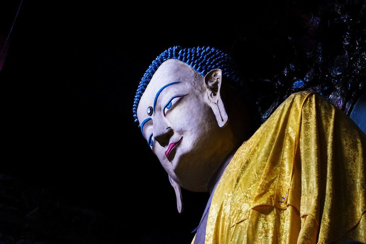 Low angle view of buddha statue against dark sky