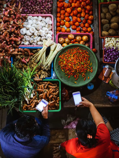 High angle view of man and woman using phone at vegetable shop