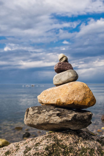 Stack Of Stones On Rock By Sea Against Sky