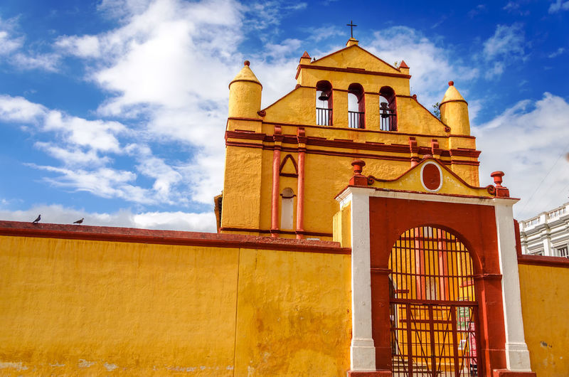 Low angle view of closed yellow iglesia de san nicolas entrance against sky
