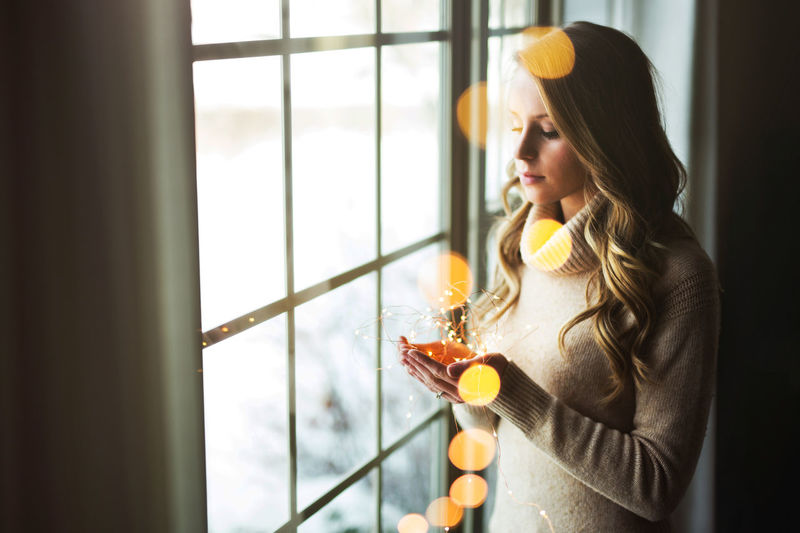Christmas Christmas Lights Adult Adults Only Beautiful Woman Day Drink Drinking Drinking Glass Food And Drink Holding Home Interior Indoors  One Person One Woman Only One Young Woman Only Only Women Orange Juice  People Real People Window Young Adult Young Women
