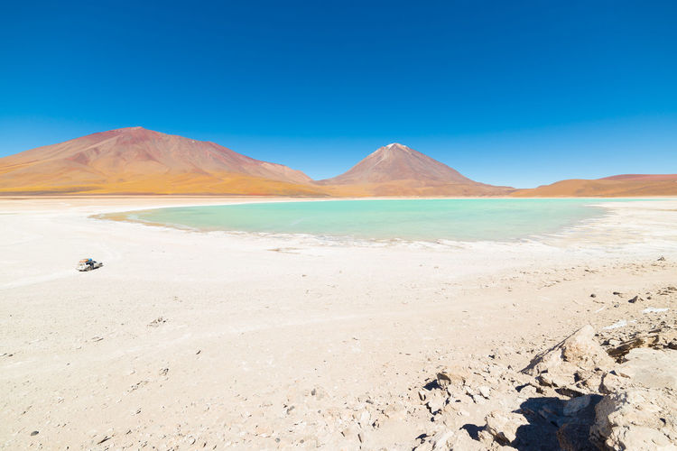 "Wide angle view of the outstanding Green Lagoon or ""Laguna Verde"", a frozen salt lake on the way to the famous Uyuni Salt Flat, travel destination in Bolivia. Snowcapped Licancabur Volcano, 5920 m, in the background. Keywords: laguna verde,bolivia,lake,adventure,desert,volcano,licancabur,salt lake,people traveling,andes,exploration,travel destination,frozen,mountain range,barren,Landscape,Majestic,uyuni,lagoon,rocky mountains,Panoramic,Travel,extreme terrain,mineral,pond,water,green,Mountain,chile,ice,wilderness area,peru,cold,south america,atacama,argentina,frost,clear sky,flat,plateau,water surface,beauty,Nature,outdoors,remote,Scenics,Idyllic,sky,horizon,wide-angle Arid Climate Beauty In Nature Blue Clear Sky Day Desert Flamingo Landscape Mountain Nature No People Outdoors Salt - Mineral Salt Basin Salt Flat Sand Sand Dune Scenics Sky Tranquil Scene Tranquility Water"
