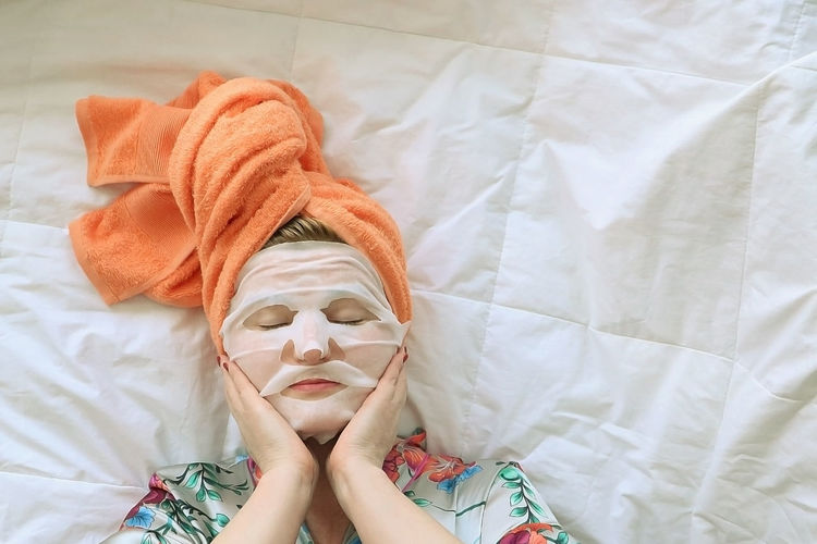 Young woman in orange towel on her head after bath doing self-care procedures at home