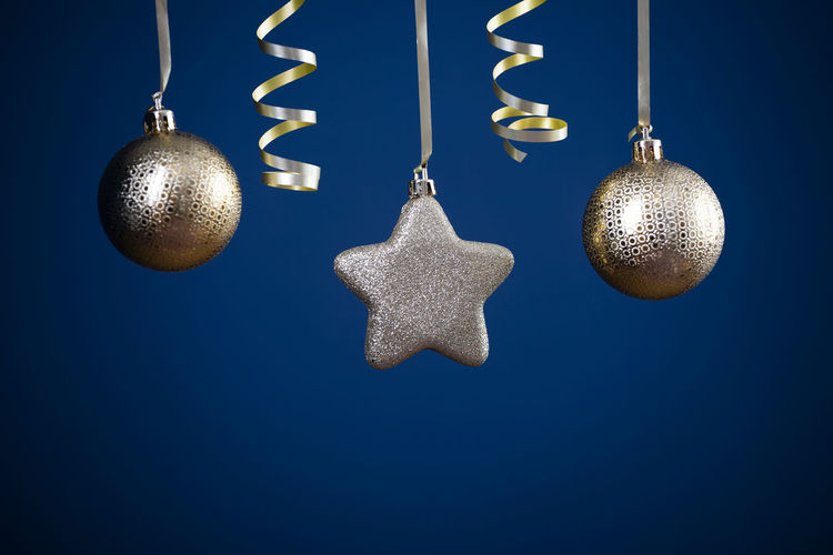 Close-up of christmas decorations hanging against blue background
