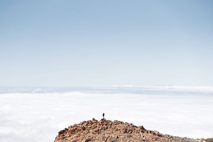 Distant view of person standing on mountain against sky