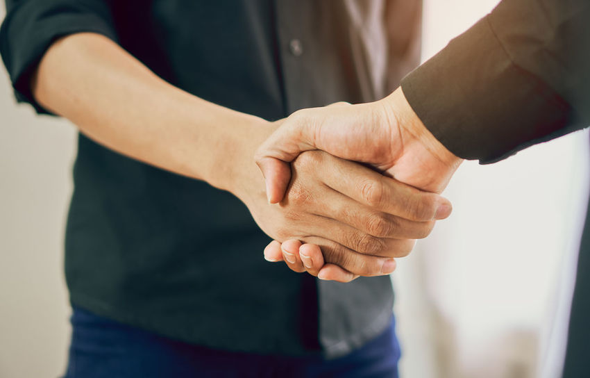 Joint Hands of Two Businessmen After Negotiating a Successful Business Agreement, And the handshake together. This is to promote cooperation in the joint business. Teamwork planning Brainstorming Business Congratulations Growth Happy Interview Meeting Office Teamwork Working Acquisition Agreement Commerce Cooperation Deal Financial Friendship Handshake Partnership People Professional Shake Success Successful Togetherness