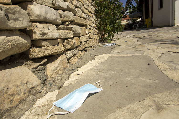 Damaged wall by footpath in city