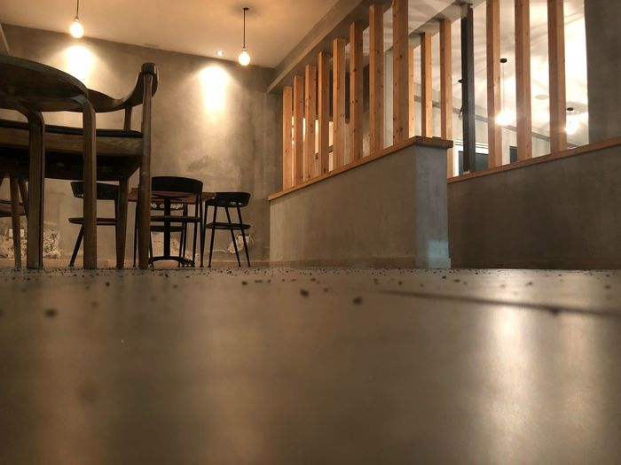 Low angle view of tables and chairs in empty cafe