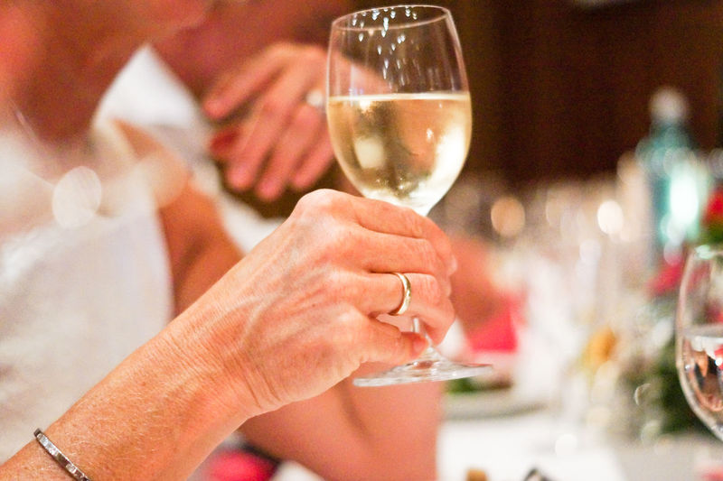 Close-Up Of Hand Holding Glass Of Wine In Restaurant
