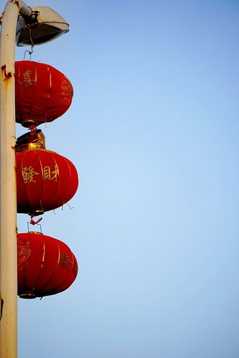 Low Angle View Of Red Lanterns Hanging From Street Light Against Clear Sky