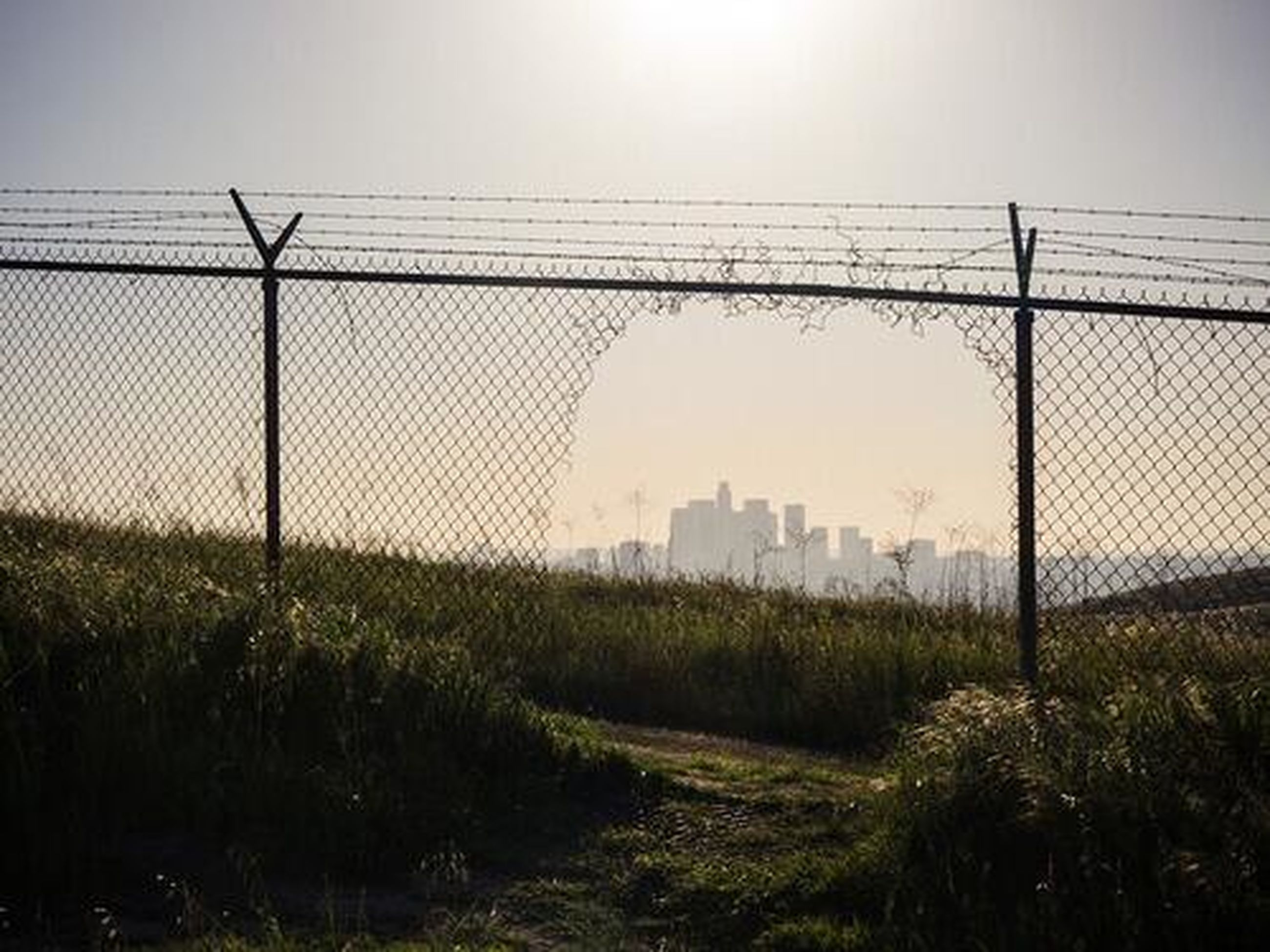 fence, built structure, field, architecture, chainlink fence, protection, safety, security, clear sky, grass, electricity pylon, sky, barbed wire, building exterior, connection, landscape, fuel and power generation, metal, power line, outdoors