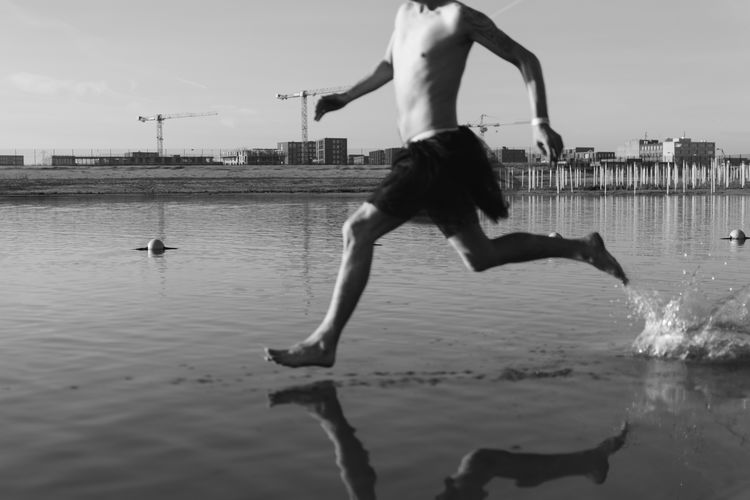 Low section of man running at beach against sky