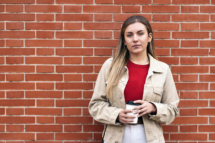 Portrait of young man holding coffee while standing against brick wall