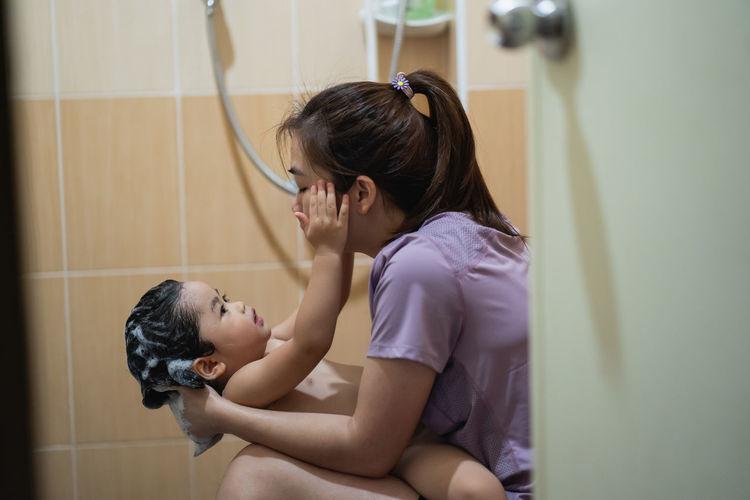 Side view of mother showering daughter in bathroom