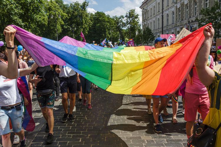 People on multi colored umbrellas on street in city