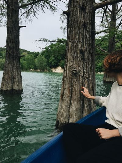 Woman sitting on tree trunk by lake
