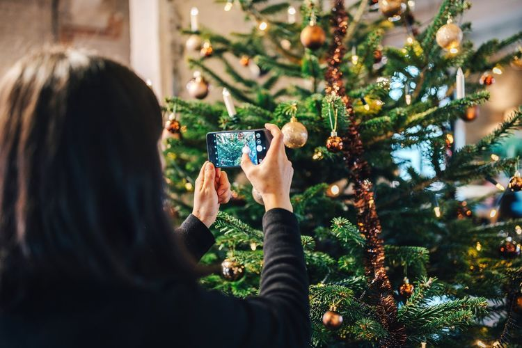 Rear view of woman photographing christmas tree