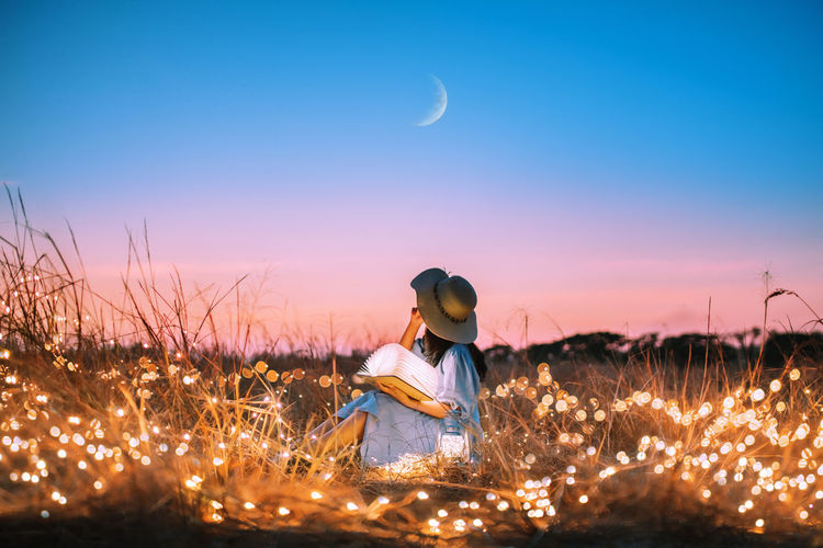 We shine together like the moon & Stars 🌛🌟 . Young woman looking at the moon in the grass field with Fairy Lights background. Nightphotography Night Moonlight Lights Light Light And Shadow Innocence Lifestyles Beauty In Nature Moon Women Girls Casual Clothing Field Leisure Activity Land Real People Plant Nature Childhood Sunset Child Sky One Person