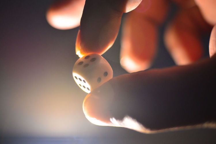 Close-up of hand holding a dice at night