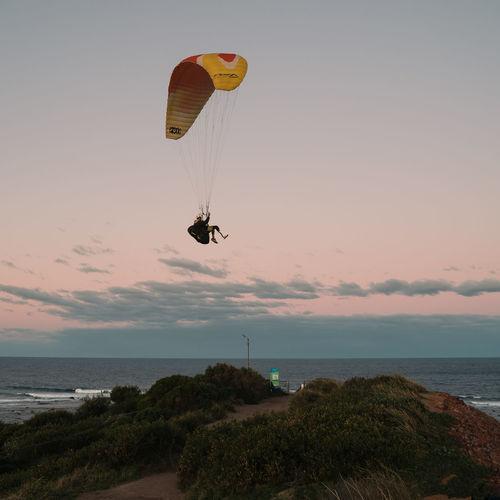 Kite flying over sea against sky during sunset
