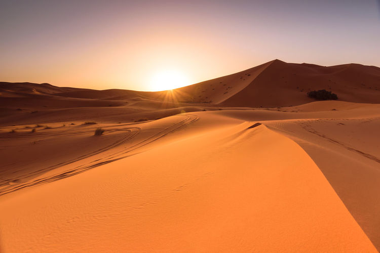 A beautiful sunrise at the dunes of Erg Chebbi located in the Sahara, Morocco. Africa Arid Climate Desert Dune Erg Chebbi Hot Landscape Merzouga Morocco Nature No People Orange Outdoors Remote Sahara Sand Sandy Sky Summer Sunlight Sunrise Sunset Tranquility Travel Travel Destinations