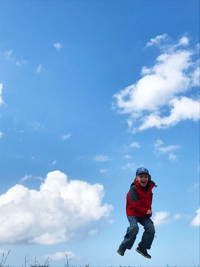 Low angle view of boy against sky