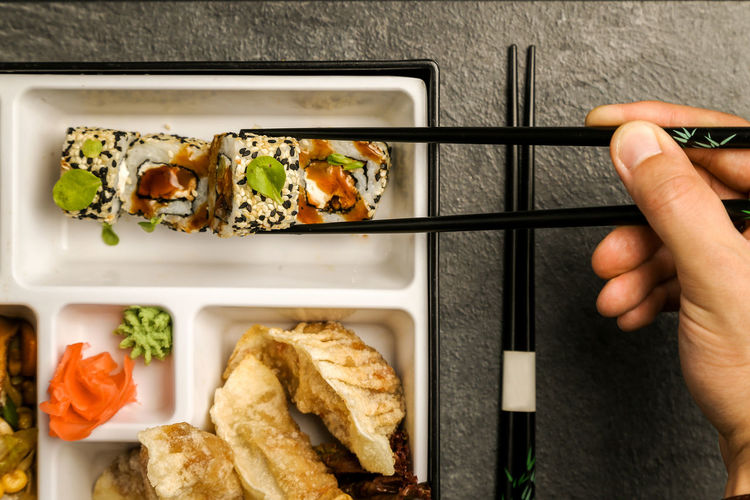 Cropped Image Of Hand Holding Sushi With Chopsticks In Plate