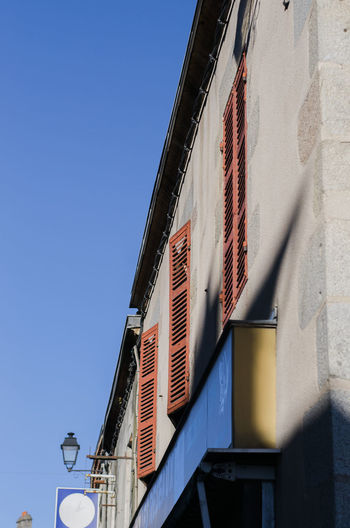 Red shutters on a traditional French building against a blue sky. France Architecture Blue Blue Sky Building Exterior Built Structure Clear Sky Day Low Angle View No People Outdoors Shutter Sky Traditional Window