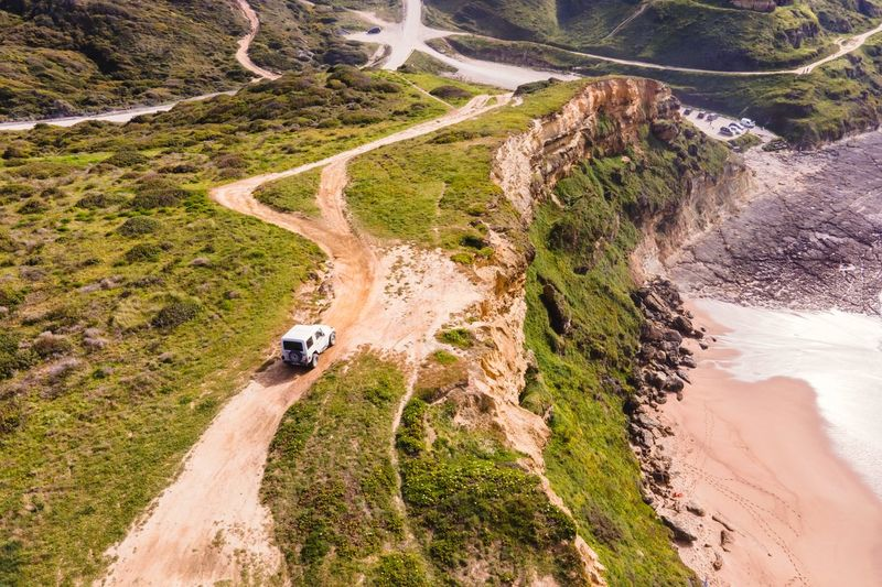 Aerial view of a four wheel drive car parked on the top of the cliff facing the atlantic ocean