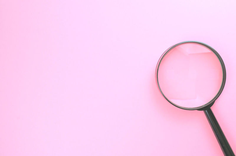 Close-up of magnifying glass over pink background