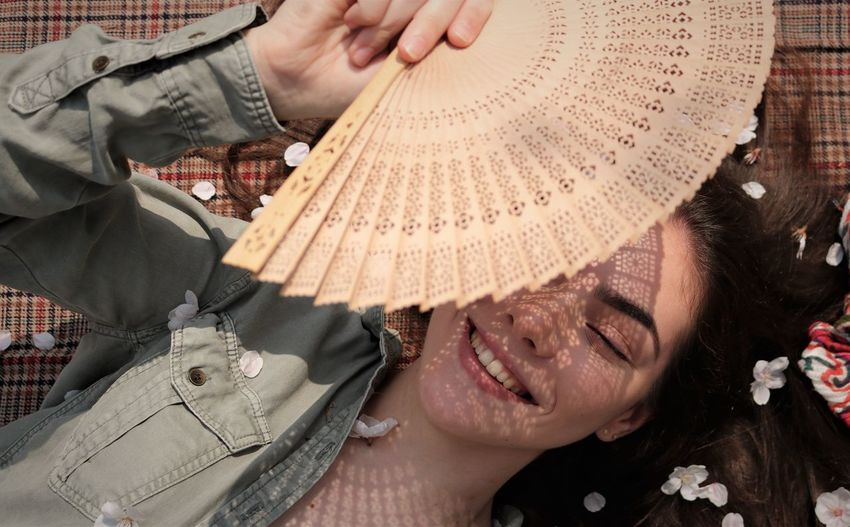 Directly above shot of smiling girl holding hand fan while lying on textile