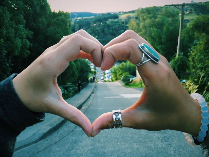 Cropped hands of people making heart shape against trees
