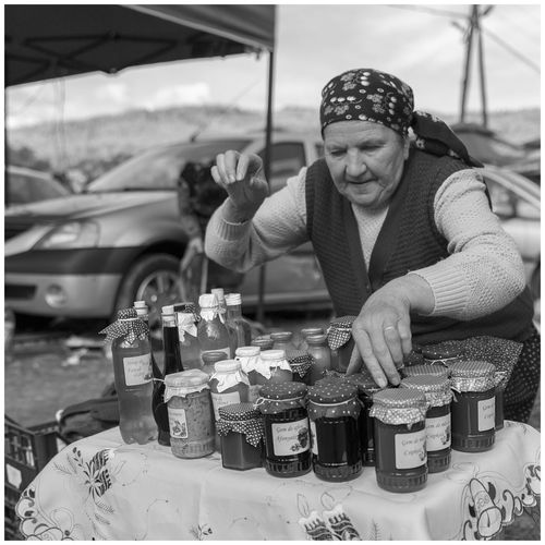Home-made Food  Black And White Friday Blackandwhite Photography Day Food Home-made Marmalade Lifestyles Marketplace Marmalade Mature Adult Mature Woman Monochrome Photography Negreni Occupation One Person Open Market Outdoors People Real People Selling Working The Portraitist - 2018 EyeEm Awards