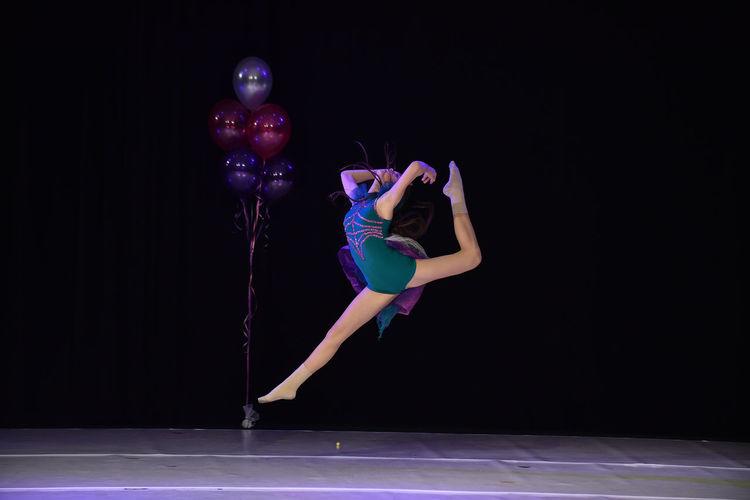 Full length of teenage girl dancing on stage
