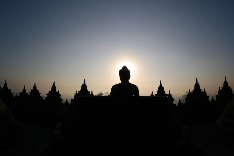 Low angle view of statue at temple against sky during sunset