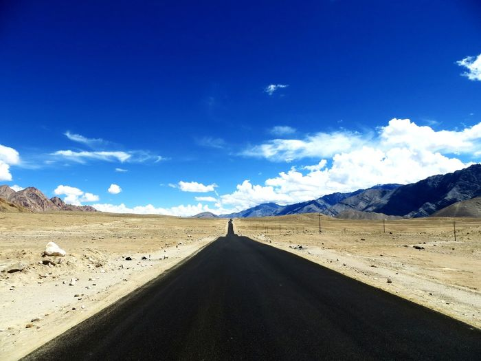 Road Amidst Desert Against Blue Sky