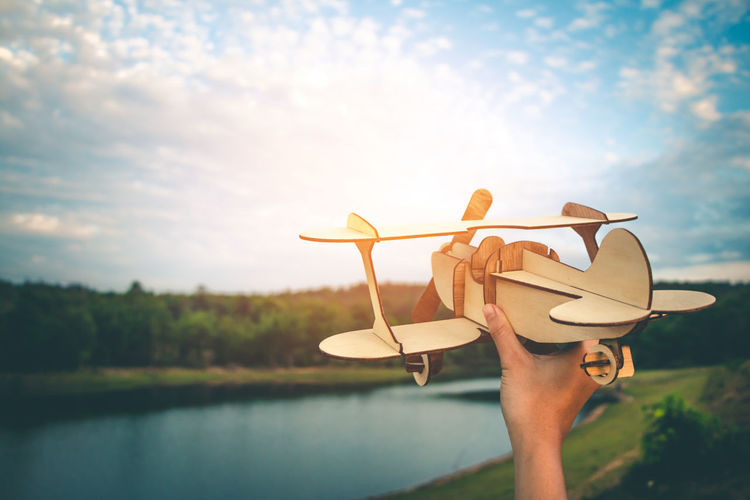 Cropped hand holding model airplane by lake