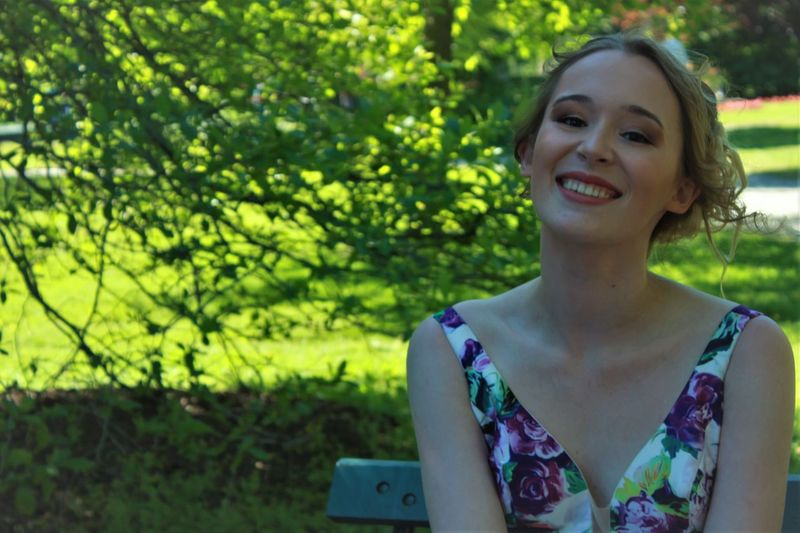 Portrait Of Smiling Teenage Girl Sitting Outdoors