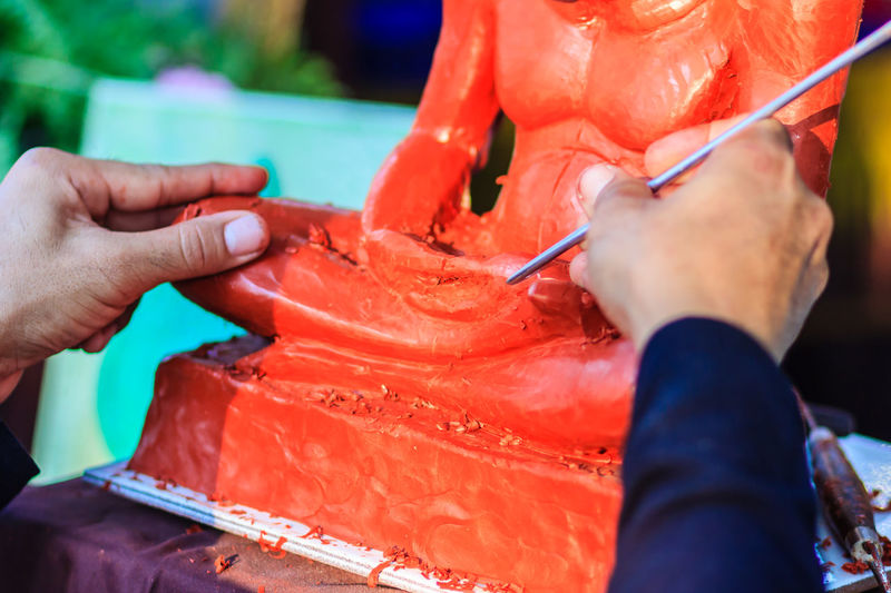 Cropped Image Of Sculptor Painting Statue