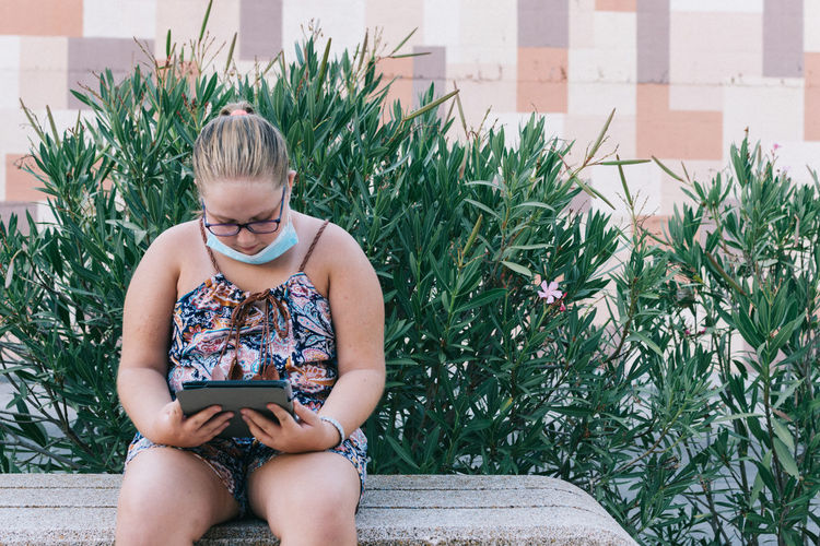 Girl with glasses playing with a tablet. sitting on a park bench.