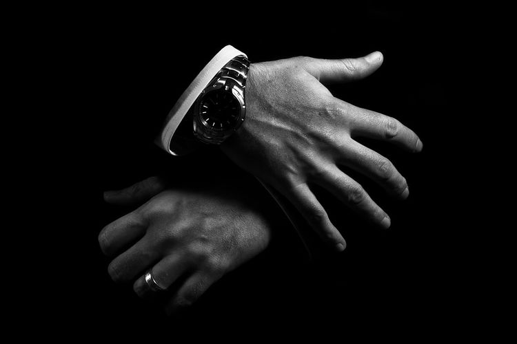 Cropped Hands Of Man Wearing Watch Against Black Background