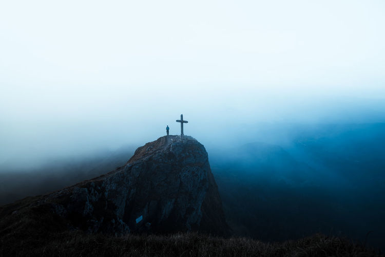 View of cross on mountain against sky