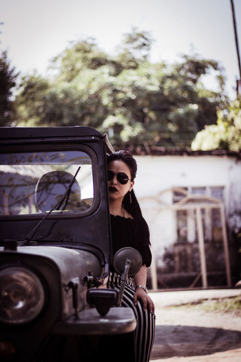 Portrait of beautiful young woman sitting on off-road vehicle