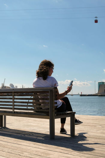 Portrait of a young woman sitting on a bench and looking at her smartphone in the port of Barcelona with the red cabin of a cableway in the background Barcelona Barcelona, Spain EyeEmNewHere Red Bench Cableway Casual Clothing Clear Sky Day Full Length Leisure Activity Lifestyles One Person Outdoors Real People Relaxation Seat Sitting Sky Smartphone Sunlight Technology Water