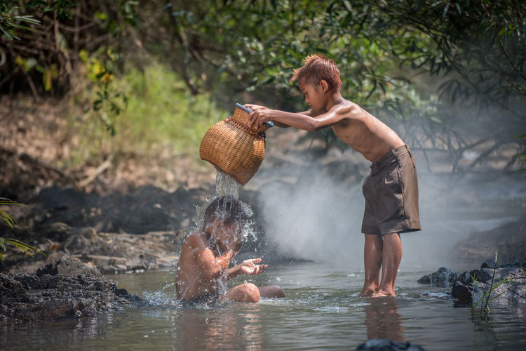 Side view of shirtless boy holding water in river