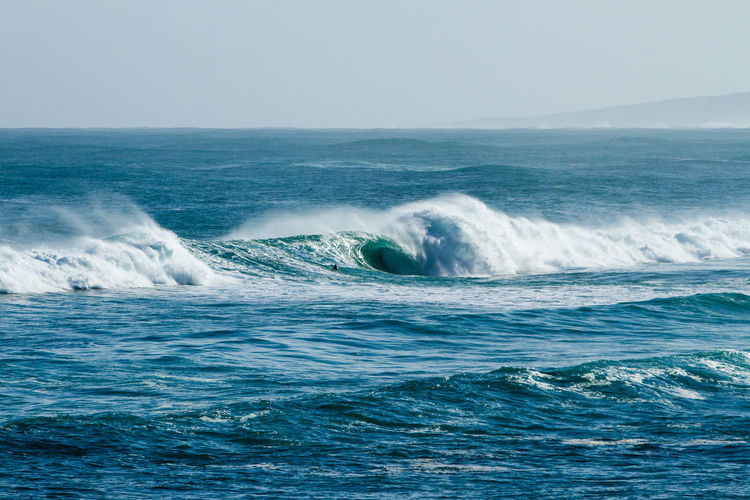 Scenic view of wave rushing sea against clear sky