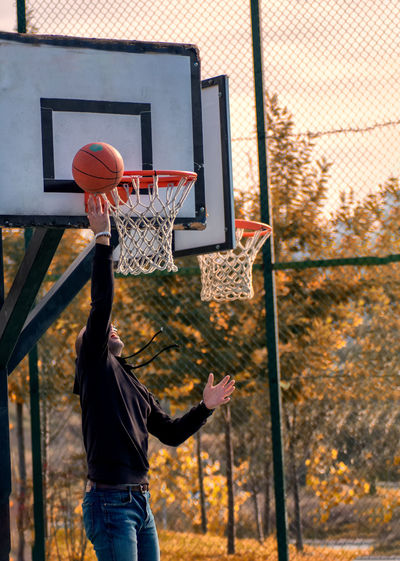 Man playing with basketball hoop