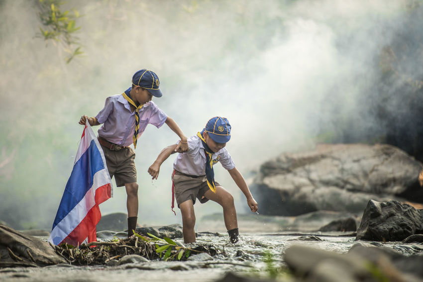 Adventure scout hold a flag team in the camping Adventure ASIA Asian  Boys Brother Cape  Child Childhood Children Only Day Flag Friendship Full Length Males  Nature Nature Outdoors People Scout Scouts Student Sword Thai Togetherness Two People