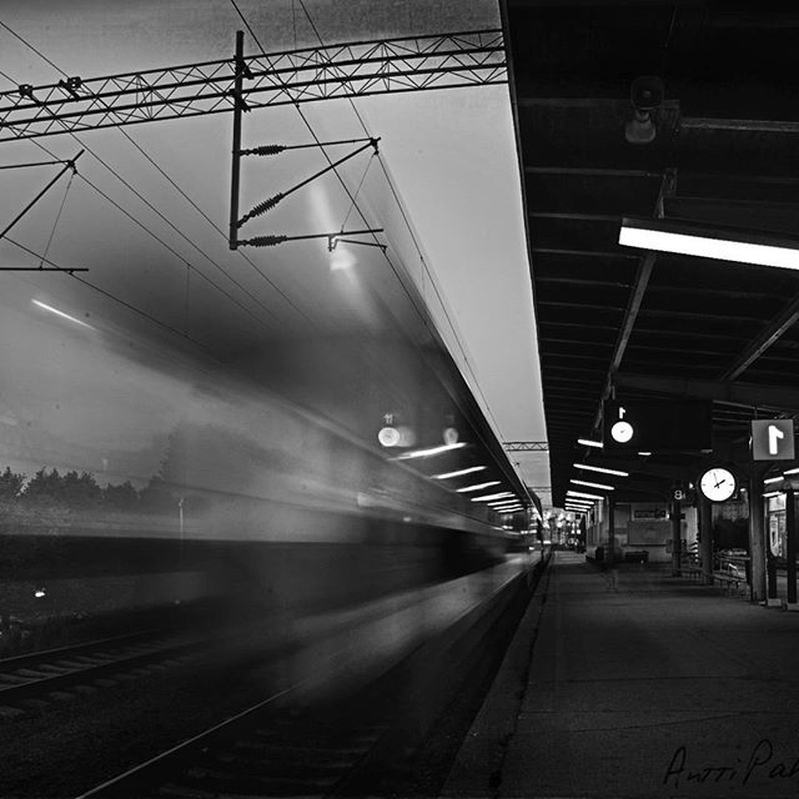 transportation, railroad track, rail transportation, public transportation, railroad station platform, railroad station, the way forward, diminishing perspective, illuminated, mode of transport, built structure, train - vehicle, power line, architecture, travel, vanishing point, electricity, on the move, railway track, motion