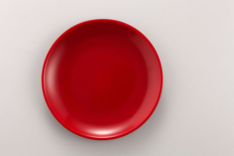 Directly above shot of empty red glass against white background